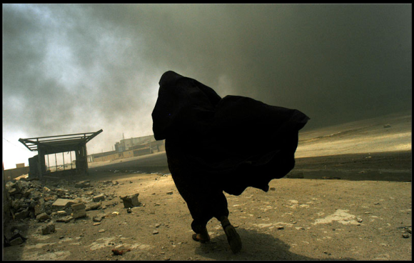 Lynsey Addario, BASRA, IRAQ.  An Iraqi woman walks through a plume of smoke rising from a massive fire at a liquid gas factory as she searches for her husband in the vicinity of the fire in Basra, Iraq, May 26, 2003.