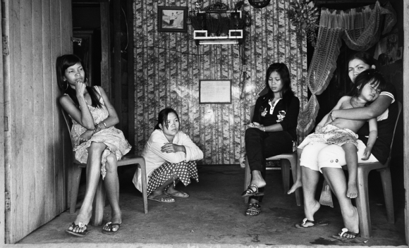 SREYNOT SEAG (far left), 23 years old, Preakabash District, Takeo Province. After a divorce from her husband, she had to quit school and become a prostitute in order to support herself. She has been a sex worker for three months. In two years, she hopes to have enough money to go back to school and learn the beauty salon trade.